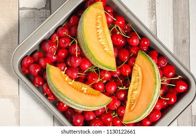 Honeydew melon and cherry fruits on wooden table