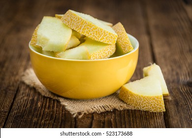 Honeydew Melon on an old wooden table as detailed close-up shot (selective focus)