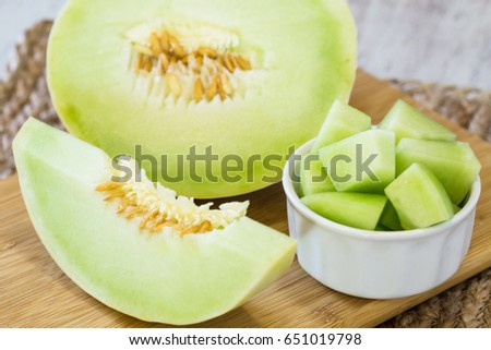 Honeydew melon slice and cut up pieces for breakfast snack diet food on cutting board