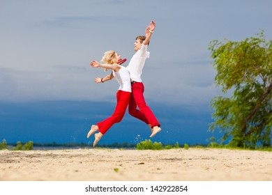Honeymoon. Beautiful young couple on the beach. Loving couple having fun on nature. Love, romance, fun. Sea trip. Red and white clothes.