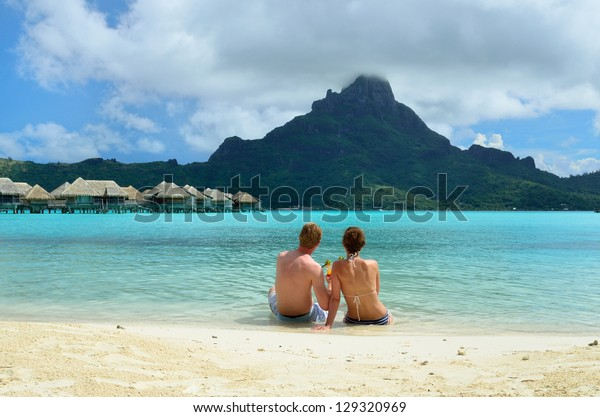 A honeymoon couple drinking a cocktail on the beach of a luxury vacation resort in the lagoon with a view on the tropical island of Bora Bora, near Tahiti, in French Polynesia.