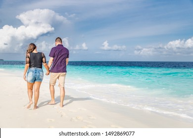 Honeymoon couple holding hands walking on perfect white sand beach. Travel vacation concept. Newlyweds happy in love relaxing on summer holidays in sunny tropical paradise destination