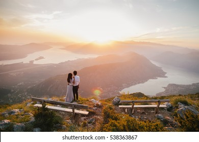 honeymoon couple kiss and embrace at sunset at sunset silhouette. Mountains and sea view on Kotor Bay. Montenegro