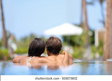 Honeymoon couple relaxing together in an infinity swimming pool in luxury resort spa retreat beach destination. Luxurious hotel travel vacation. Unrecognizable people relaxed enjoying summer holidays.