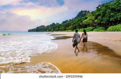 Honeymoon couple take a walk at the scenic Havelock islands beach at Andaman India.