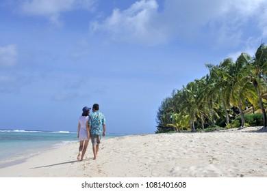 Honeymoon couple walks on a tropical pacific island beach in Rarotonga, Cook Islands. Real people. Copy space