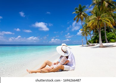 A honeymoon couple in white summer clothes sits hugging on a tropical paradise beach in the Maldives and enjoys their vacation time