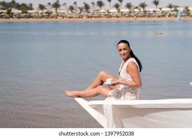 Honeymoon cruise ship. Wedding ceremony sea cruise. Bride adorable white wedding dress sunny day sit on boat or ship. Girl enjoy coffee sea cruise. Exotic vacation honeymoon. Honeymoon ideas.