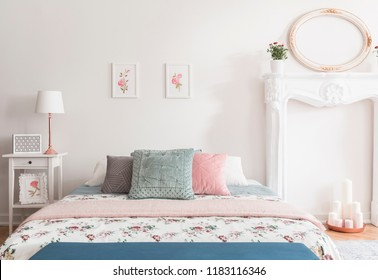 Honeymoon romantic bedroom interior in English style with rose pattern on a bed cover and illustrations on the wall. Real photo.