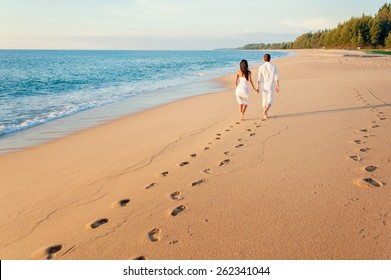 Honeymoon at the sea. Back view of loving couple walking away with footprints at sandy beach