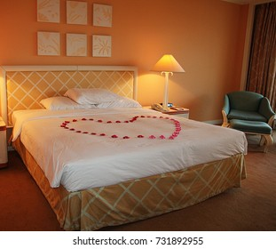 Honeymoon suite in a modern hotel room with king-sized bed and flowers formed into a giant heart