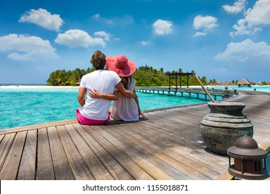 Honeymoon traveller couple hugging on a wooden jetty and enjoys their tropical holiday in the Maldives islands