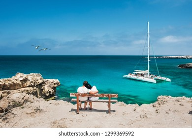 Honeymoon traveller couple hugging on a wooden bench and enjoys their tropical holiday. Wedding travel. Young happy couple sitting back on beach. Rear view of a couple in love on vacation. Travelers