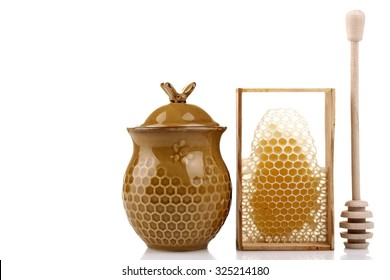honeypot and spoon for honey near honey combs on white isolated background