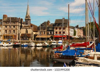 Honfleur city Harbour during spring with sailing boats, color old Norman houses and their reflection in water. Normandy, France.