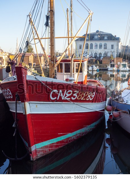 Honfleur / France - 12 30 2019: Red boat in the port of Honfleur at the street called Quai Sainte-Catherine. Christmas market in the background in front of the Hotel de Ville.