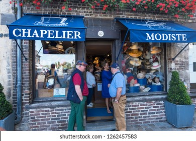 Honfleur, France - August 20, 2018: Several men await their women near the hat shop in Honfleur. Normandy, France