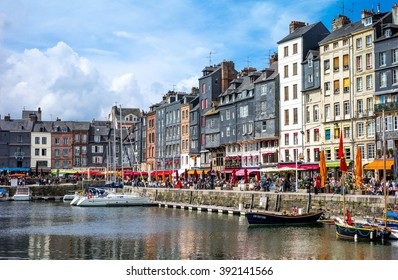Honfleur, France - May 19, 2012: Normandy, traditional houses and boats in the old harbor basin.