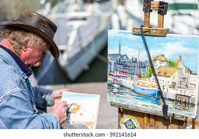 Honfleur, France - May 19, 2012: Normandy, a street painter in the old harbor basin.