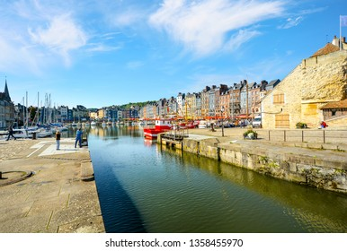 Honfleur, France - September 15 2018: Tourists take a photo of the picturesque old port of Honfleur, France along the Normandy coast of the English Channel.
