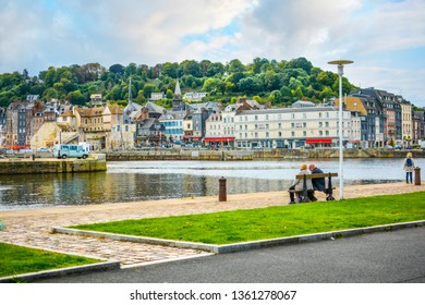 Honfleur, France - September 15 2018: An older retired couple sit on a park bench and enjoy the views of the fishing village of Honfleur France, in Normandy on a partly cloudy afternoon