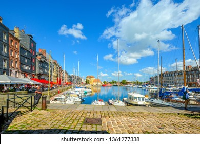 Honfleur, France - September 17 2018: A worker from a sidewalk cafe takes a break at the picturesque fishing village on the Normandy coast of France, Honfleur, with boats docked in the harbor behind