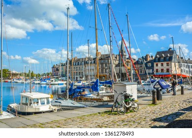 Honfleur, France - September 17 2018: Two bicycles parked along a cobblestone road as boats line the harbor on the Normandy coast of France in the Old Pier at Honfleur, France.