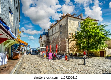 Honfleur, France - September 18 2017: Tourists at a sidewalk cafe in front of souvenir shops and the Lieutenance d' Honfleur building on a sunny summer day in the coastal village of Honfleur, France