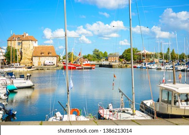Honfleur, France - September 18 2017: Boats, yachts and fishing vessels line the old harbor or Vieux Bassin in the Normandy village of Honfleur, France on a sunny summer day.