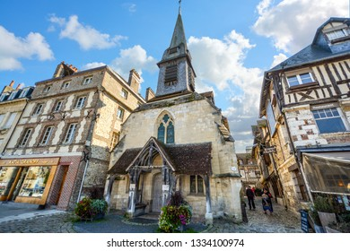 Honfleur, France - September 18 2018: Tourists walk along a narrow cobblestone path alongside the medieval Maritime Museum, in the coastal city of Honfleur, France