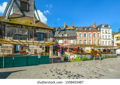Honfleur, France - September 18 2018: The market outside the Church of Saint Catherine selling fresh produce and groceries in the town of Honfleur France on a sunny day in early autumn
