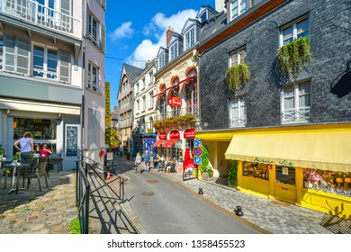 Honfleur, France - September 18 2018: Tourists enjoy the sidewalk cafes and colorful shops in the coastal fishing village of Honfleur, France, on the Normandy Coast.