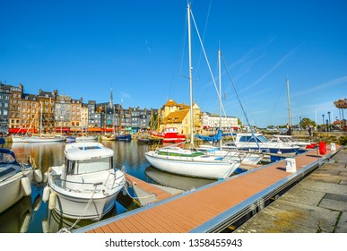 Honfleur, France - September 18 2018: Boats, yachts and fishing vessels line the old harbor or Vieux Bassin in the Normandy village of Honfleur, France on a sunny summer day.