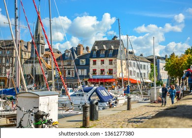 Honfleur, France - September 18 2018: The picturesque old pier and harbor at Honfleur, France, on the Normandy Coast of the English Channel on a sunny afternoon as a couple stroll by