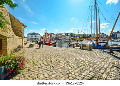 Honfleur, France - September 18 2018: Two couples, one young and one older, walk towards each other along the cobblestone roads at the old pier in Honfleur, France, past sailboats and flowers.