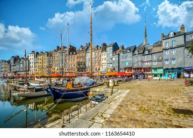 Honfleur, France - September 19 2017: Picturesque and quaint medieval harbour at the Normandy village of Honfleur France with boats, sailboats, cafes and tourists shopping the coastal village