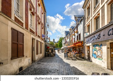 Honfleur, France - September 19 2018: Tourists having lunch at a sidewalk cafe on a picturesque back street in the Normandy village of Honfleur, France.
