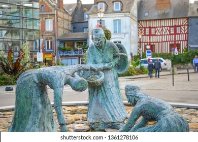 Honfleur, France - September 19 2018: The mussel gatherers statue, Les moulieres d'honfleur in the medieval fishing village of Honfleur France with half timbered homes behind
