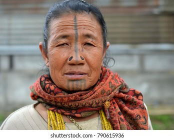HONG, ARUNACHAL PRADESH, INDIA - OCT 22, 2017: Old Apatani woman with black wooden nose plugs (yaping hullo) and distinctive tribal face tattoo poses for the camera in Ziro Valley, on Oct 22, 2017.