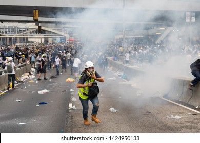 Hong Kong 12th June 2019: Anti Extradition Bill Protest. A reporter running for cover as tear gas canisters explode during clashes with protesters outside the Central Government Office in Hong Kong.