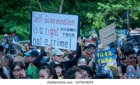 Hong Kong - 14Jul2019: Hongkongers march in Sha Tin against Hong Kong's extradition bill, unprecedented violence by riot police pepper sprayed protesters. Banner: Self-determination is a right.