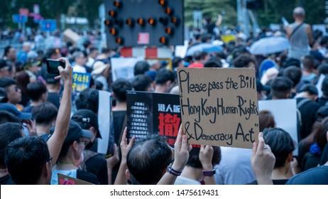 Hong Kong - 14Jul2019: Hongkongers march in Sha Tin against Hong Kong's extradition bill, shaken by unprecedented violence by police. Banner: Please pass bill: Hong Kong Human Rights & Democracy Act