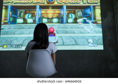 Hong Kong, 19 May 2017 -:Woman playing mario kart 8 on Nintendo Switch console over projector screen