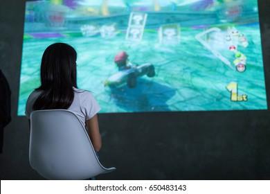 Hong Kong, 19 May 2017 -:Woman playing mario kart 8 on Nintendo Switch console over big screen