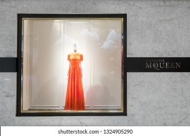 HONG KONG - 23 JAN, 2015: Alexander Mcqueen fashion boutique display window with mannequin dressed in haute couture luxury red female dress