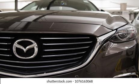 Hong Kong, Hong Kong - 25 April 2018: Close-up of Mazda logo badge, headlights and car grill on grey Mazda 6 luxury sports sedan.
