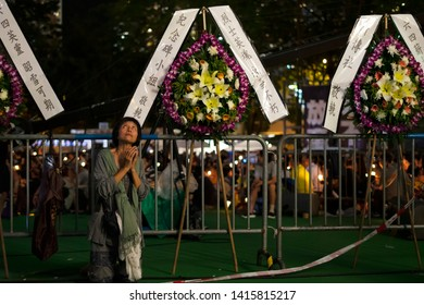 HONG KONG, 4 JUNE, 2019: A woman pray during the vigil. Large crowds turned out at the Victoria Park   attending a candlelight vigil for the 30th anniversary of Tiananmen crackdown.