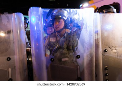 Hong Kong 9th June 2019: A riot police officer behind his riot shield as the police prepare to clear protesters away from government offices.