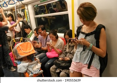 HONG KONG - APR 27, 2014: Unidentified passengers use mobile phones in subway. Mobile phones and tablets are used for people to entertain and view information when they take public transportation.