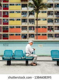 Hong Kong - April 15 2019: Choi Hung Estate Car Park, narrow apartments in the public housing estate. Most popular place for tourists. Old man sitting on a bench, turned away from crowd